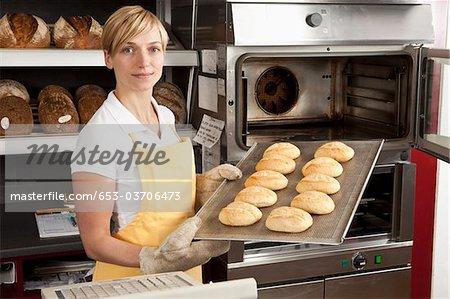 Une femme tirant sur un plateau de pains fraîchement sortis du four dans une boulangerie