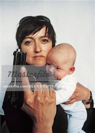 Une mère tenant une arme de poing et un bébé dans son autre bras