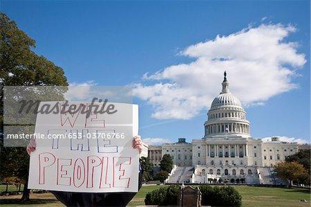 Un manifestant tenant une pancarte devant le Capitol Building