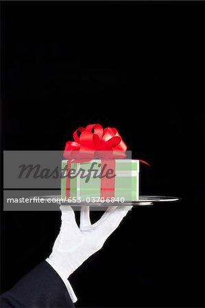 Un majordome, présentant un cadeau sur un plateau d'argent, mise au point sur place