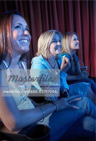 Sourire de jeunes femmes assises, regarder film dans le théâtre