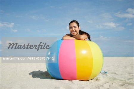 Adolescente (16-17), assis derrière le ballon de plage sur la plage, portrait