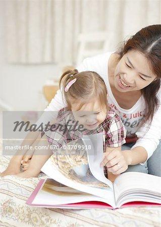 Mère et fille lisant un livre de photo