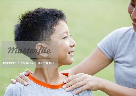 A boy put hands on his his shoulder