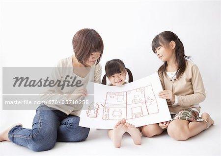 Mère et enfants, tenant un pictuere de la disposition de la salle