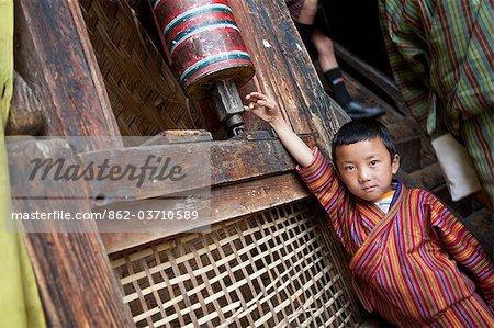 Un jeune garçon jouant avec une roue de prière au monastère de Thangbi Mani au Bhoutan