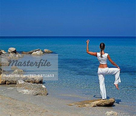 Girl practising yoga on Boussolos Beach
