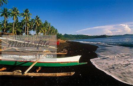 Indonesia,Sulawesi,Tangkoko. Outriggers on a Black sand beach at Tangkoko.