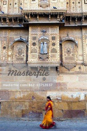 Indien, Rajasthan, Jaisalmer. Leben auf der Straße geht auf die äußeren Wände der Stadt größte Haveli, auf so normal wie ein Sari bekleideten Frau geht neben den stark verzierten Wänden.