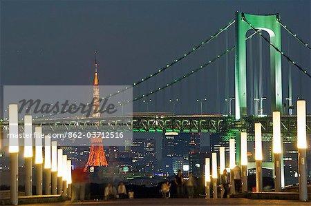 Rainbow Bridge et la tour de Tokyo, les gens au premier plan en prenant une promenade en soirée.