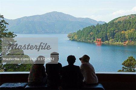 Japan,Honshu Island,Kanagawa Prefecture,Fuji Hakone National Park. Red Torii Gate on Lake Ashi with Mount Fuji (3776m) in background. Japanese women viewing from Narukawa Museum.