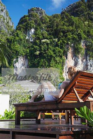 Woman sitting on sun lounger by pool in Bhu Nga Thani Resort and Spa, Railay, Krabi Province, Thailan.