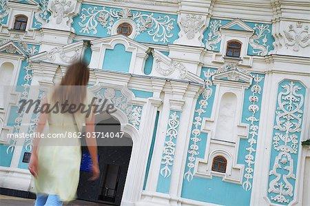 Woman walking towards bell tower at St Sophia's Cathedral, Kiev, Ukrain.