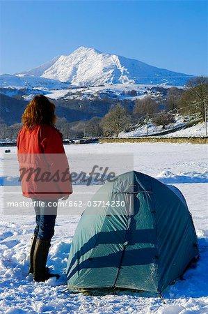 Wales, Gwynedd, Snowdonia. A camper by her tent looking towards Moel Siabod.