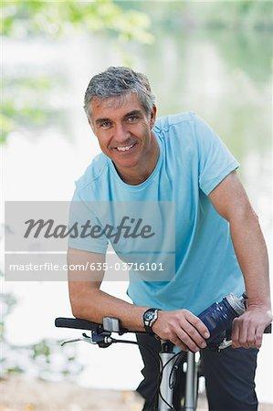 Homme debout avec vélo souriant