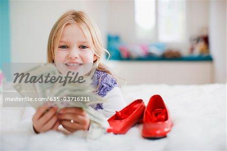 Jeune fille souriante tenant des billets d'un dollar