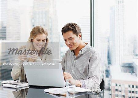 Geschäftsleute mit Laptop zusammen