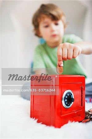 Boy putting coin into safe piggy bank