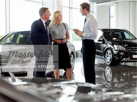 Salesman talking to couple in automobile showroom