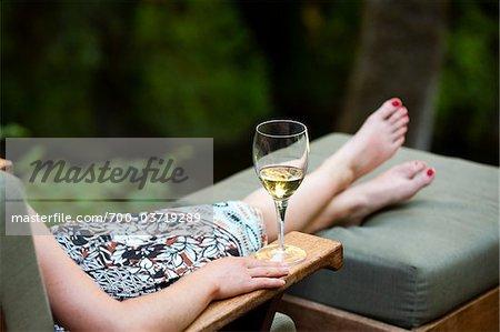 Femme reposante sur une chaise longue avec verre de vin