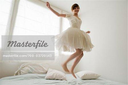 Junge Mädchen, Teenager, Spaß zu haben, springen auf dem Bett in ihrem weißen Ballerina Kleid vor Fenster, Salzburg, Österreich, Herrn ja, PR nicht,