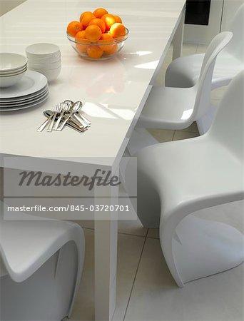 Maison à Chelsea, à Londres. Table à manger moderne blanc avec chaises moulées blanches en porte-à-faux et plancher blanc. Architectes : Architectes de Chris Dyson