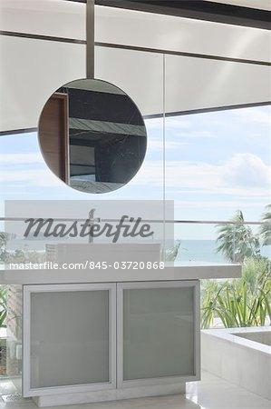Salle de bains avec miroir rond et la vue depuis les baies vitrées. Architectes : Lim Cheng Kooi et AR43