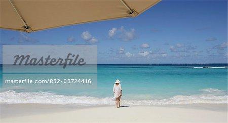 Femme debout sur une plage tropicale avec parapluie au premier plan