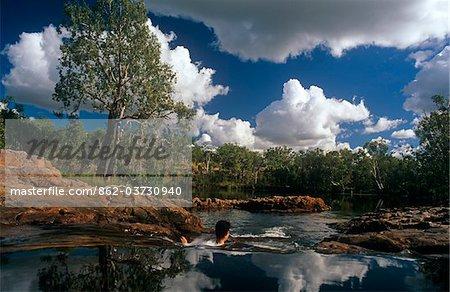 Australia, Northern Territory, Jatbula Trail, Nitmiluk National Park, nr Katherine. A walker cools off in a rock pool by Sandy Camp Pool.