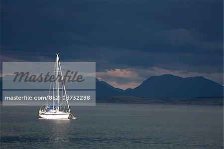 Écosse, île de Mull. Yacht ensoleillée dans le Sound of Mull contre un ciel orageux dramatique.