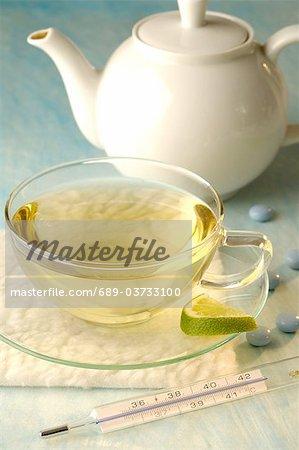 Thé avec thermomètre clinique, théière et pilules