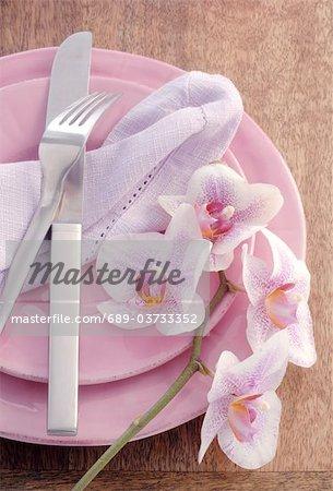 Orchidee blüht auf Teller mit Besteck
