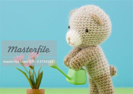 Ours en peluche tricot arrosant les fleurs