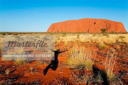 Australie, Northern Territory, Parc National d'Uluru-Kata Tjuta. Ombre sautant de joie à Uluru (Ayers Rock) au coucher du soleil. (PR)