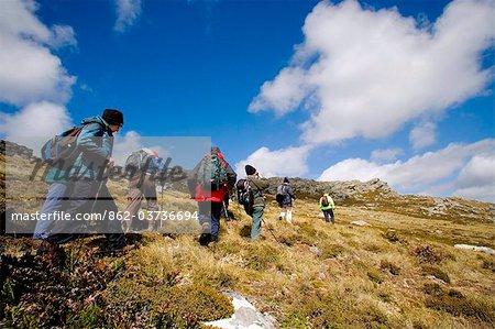 Falkland Islands. Tourists follow battleground guide Tony Smith across the slopes of Mt Tumbledown, near Stanley.