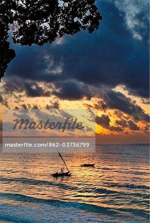 Kenya Mombassa. An outrigger canoe sets sail from Diani Beach at sunrise.