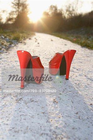 Chaussures à talons haut rouge sur le chemin de sable