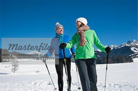 Couple marchant avec des bâtons de Ski en hiver