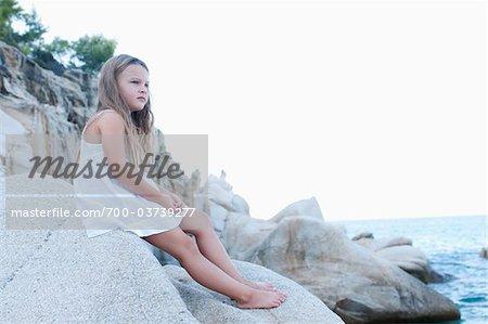 Fille assise sur les rochers à la plage