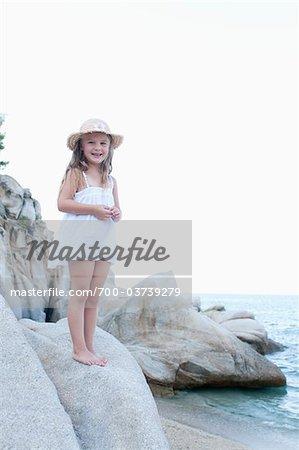 Jeune fille debout sur les rochers à la plage