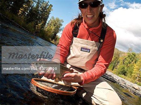 Femme détient et met en valeur une truite arc-en-ciel capturés lors de la pêche à la mouche dans le centre-sud Russian River, la péninsule de Kenai, en Alaska, automne