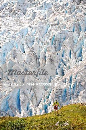 Woman hiking alongside  Exit Glacier in the Harding Icefield, Kenai Fjords National Park, Kenai Peninsula, Southcentral Alaska, Summer