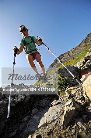 Woman with walking sticks decends the trail from Harding Icefield, Kenai Fjords National Park, Kenai Peninsula, Southcentral Alaska, Summer
