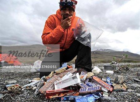 Backpacker eats snacks  at base camp along the Hulahula River, Brooks Range, ANWR, Arctic Alaska, Summer