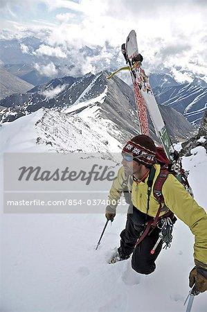 Backpacker domine la scène ci-dessous car il monte le Chamberlin crête ouest du Mont dans la chaîne de Brooks, ANWR, Arctique de l'Alaska, l'été
