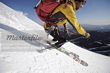 Backcountry Skifahrer macht eine Abfahrt am frühen Morgen von der Nordseite des Mount Chamberlin, Brooks Range, ANWR, Arktische Alaska, Sommer
