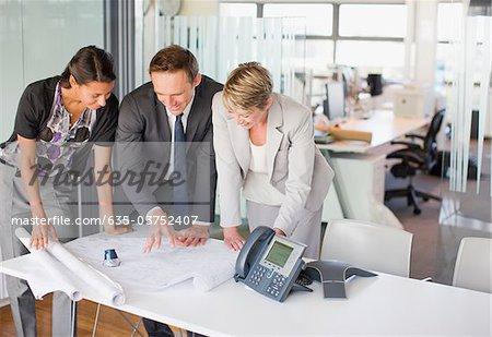 Geschäftsleute, die Überprüfung der Entwürfe zusammen im Büro