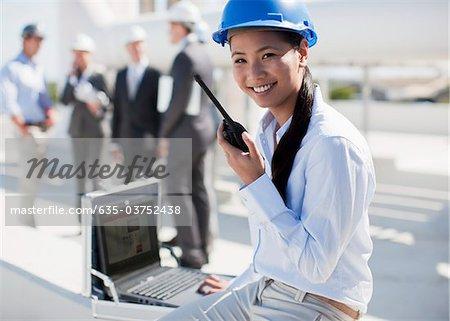 Businesswoman in hard-hat talking on walkie-talkie outdoors