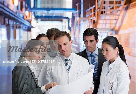 Geschäftsleute und Wissenschaftler betrachten Blaupausen in Fabrik