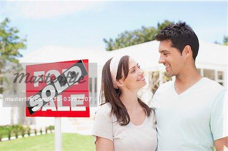 Couple Standing in der Nähe von verkauften Zeichen für ihr neues Haus